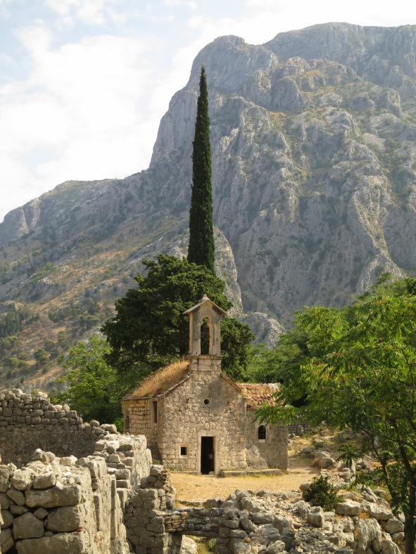 An old stone church, hidden in a valley behind the crags on which Kotor Castle stands