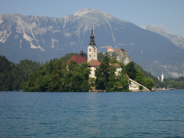 The small but exquisitely beautiful Lake Bled has a church on an island in the middle, and a tall cliff on the far bank artfully crowned with a castle